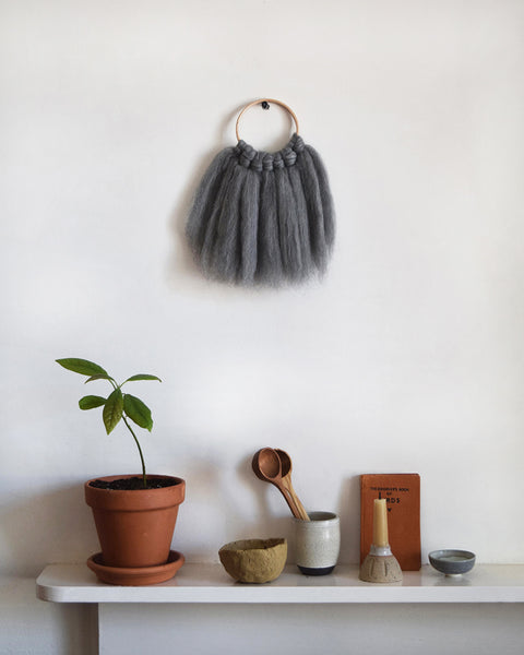 Mini woven wall hanging, designed and handcrafted in the UK from ethically sourced pure merino wool in grey.