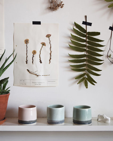 Hand thrown in a studio in Birmingham by Katie Robbins, each porcelain beaker has been glazed with a two-tone colour, using shades reminiscent of the Welsh slate mines and green hills found near Cardigan Bay.