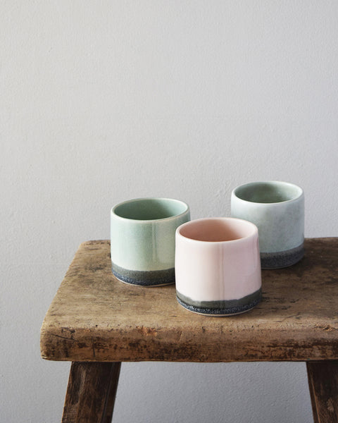 Hand thrown in a studio in Birmingham by Katie Robbins, each porcelain beaker has been glazed with a two-tone colour, using shades reminiscent of the pale pink skies at sunrise and sunset above the grey cliffs near Cardigan Bay in Wales.
