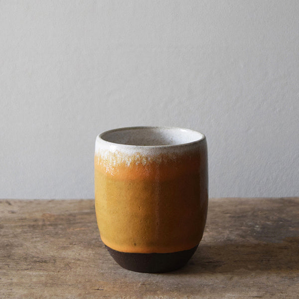 Hand thrown in a Brighton studio pottery, the beautiful slightly speckled ochre glaze reminiscent of golden summer fields, autumn colours and Sussex clay, leaves a lovely tactile orange peel texture to the beaker when holding it. Each high temperature earthenware beaker has been glazed in white on the inside to reflect the vibrant colours of your herbal teas or rich browns of your coffee, which will brighten up your mornings.