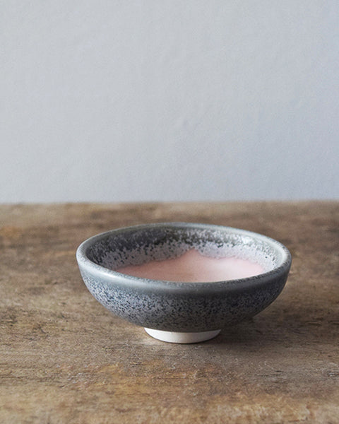 Hand thrown in a studio in Birmingham by Katie Robbins, each mini-bowl has been glazed with a two-tone colour, using shades reminiscent of the pale pink skies at sunrise and sunset above the grey cliffs near Cardigan Bay in Wales.