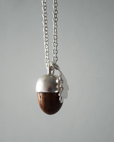 Inspired by nature, this beautiful acorn and oak leaf pendant has been designed and handcrafted in a studio in Lewes by Phoebe Jewellery. It's made from Sterling silver and hand-turned oak and has a pretty oak leaf shaped catch.