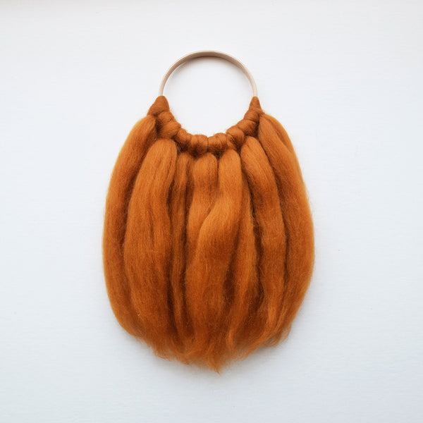 A beautiful handcrafted mini wall hanging in a gorgeous amber colour on a wooden hoop made from ethically sourced pure merino wool in mustard. We love the simplicity of the design, natural tone and super soft material, creating a cosy, nurturing environment.