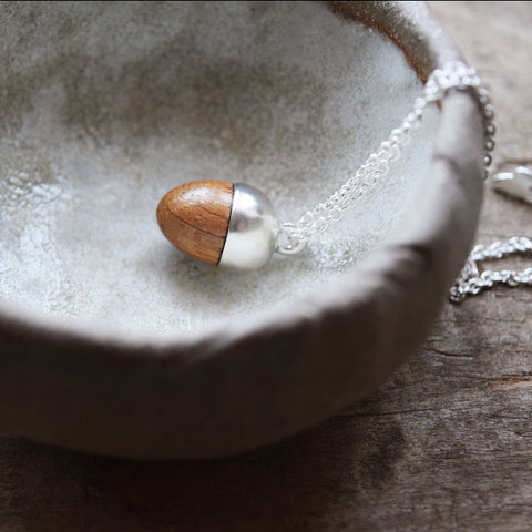 Inspired by nature, this beautiful acorn pendant has been designed and handcrafted in a studio in Lewes by Phoebe Jewellery. It's made from Sterling silver and hand-turned oak and has a pretty oak leaf shaped catch.