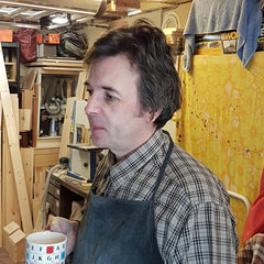 Simon in his workshop holding tea!