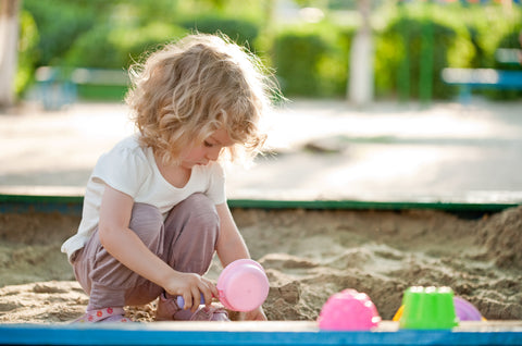 girl playing in sand, playpack