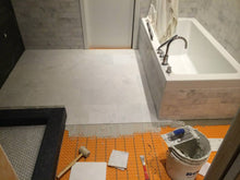 Heated floors in bathroom with white tile.