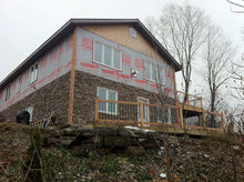 Stone facade with cedar deck for property on lake.