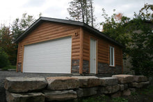 Custom detached garage renovation, with quarter log, cedar siding and ledge rock.