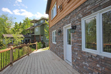 Stone facade with cedar deck.