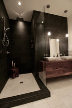 Bathroom with honed marble floor, with slate walls and walnut vanity.