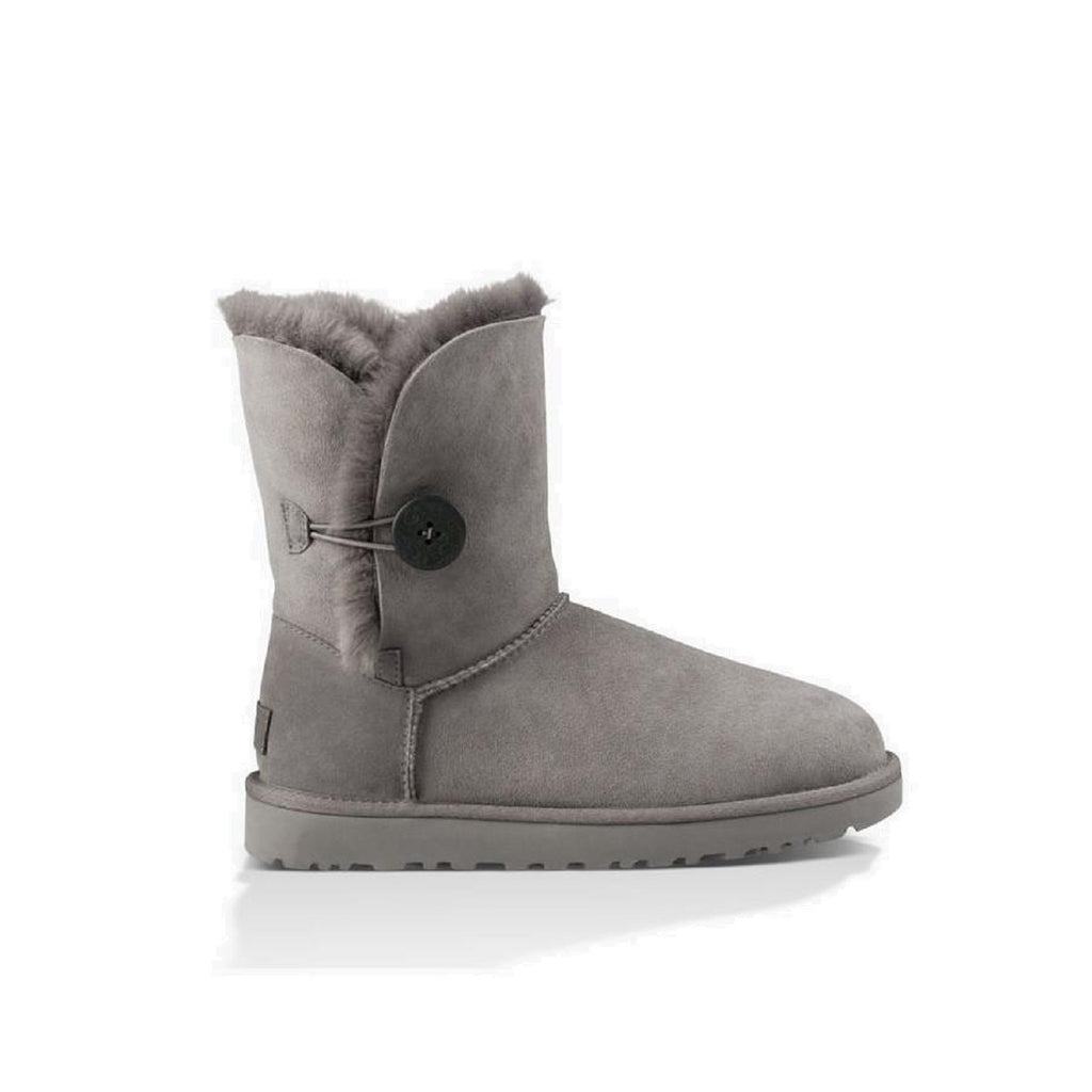 Ugg boot with button on the side and sheepskin lining inside. Color is grey.