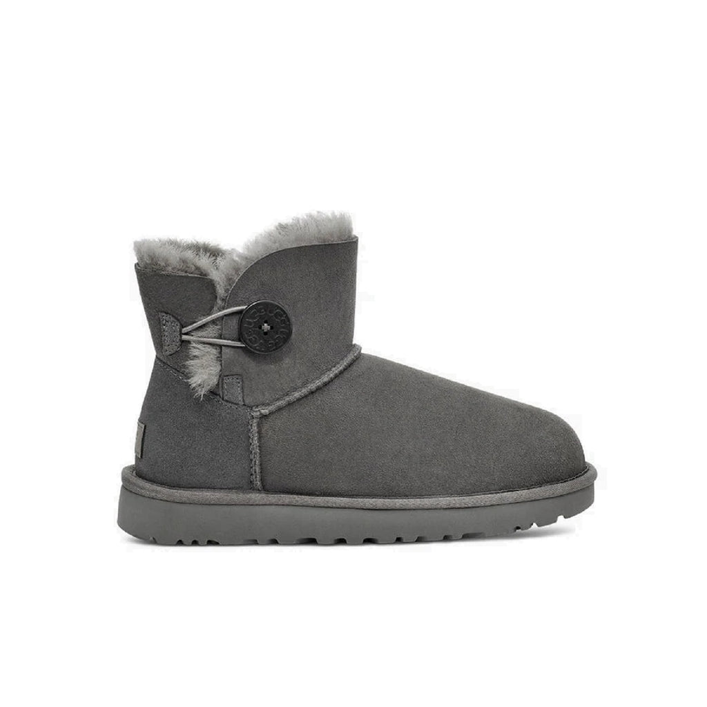 Ugg mini boot with button on the side in grey.