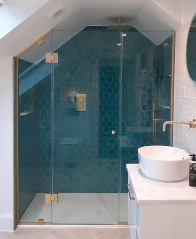 Custom shower for sloped ceiling with satin brass fixtures