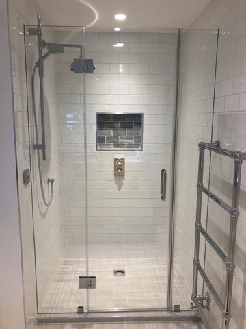 Glass shower door with side panels secured with clamps