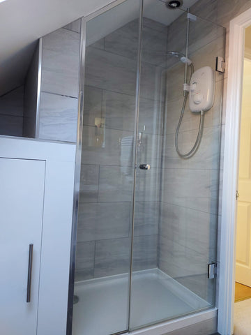 Wall hung door and shaped panel with chrome shower glass components