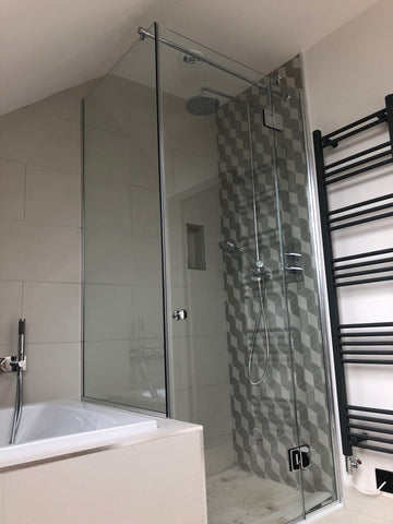 Bespoke shower glass configuration including a door and return panel on top of the bath