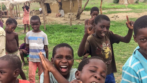 children in village in Zambia posing for camera | Kids Travel Boutique