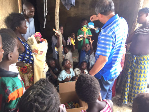 children in village in Zambia opening care box waiting their turn | Kids Travel Boutique