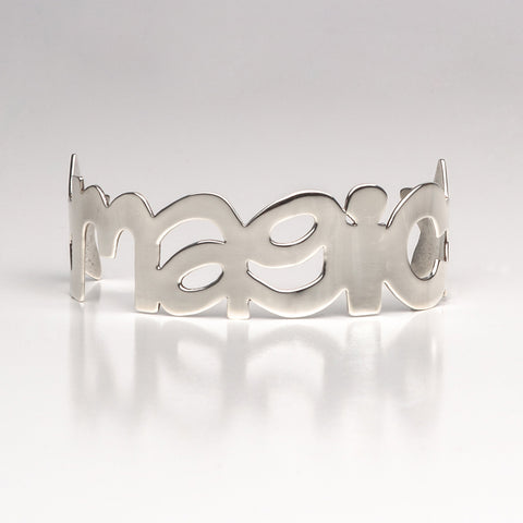 Sterling silver cuff bracelet in the shape of the word magic with a stars on either side.