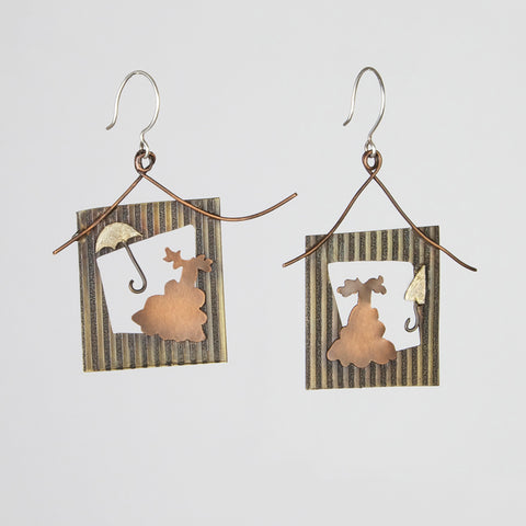 Earrings inspired by the words southern and portrait depict picture frames with ball gowns and parasols.