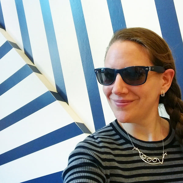 Model wears the Bean Pod Necklace and Stripe Earrings with a striped shirt in front of a wall with stripes. Sustainably made in New York by Tinker Company.