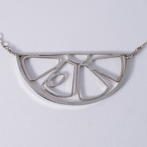 A silver pendant in the outline of a citrus fruit slice