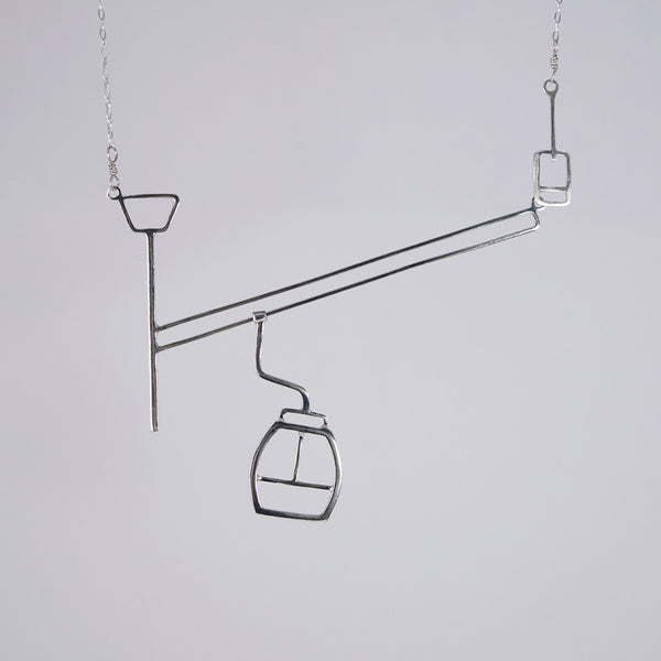 Ski lift necklace with moving gondola on a cable