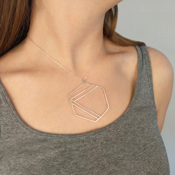 Sterling silver necklace with hexagonal shape outline and center stripe design, shown here on model