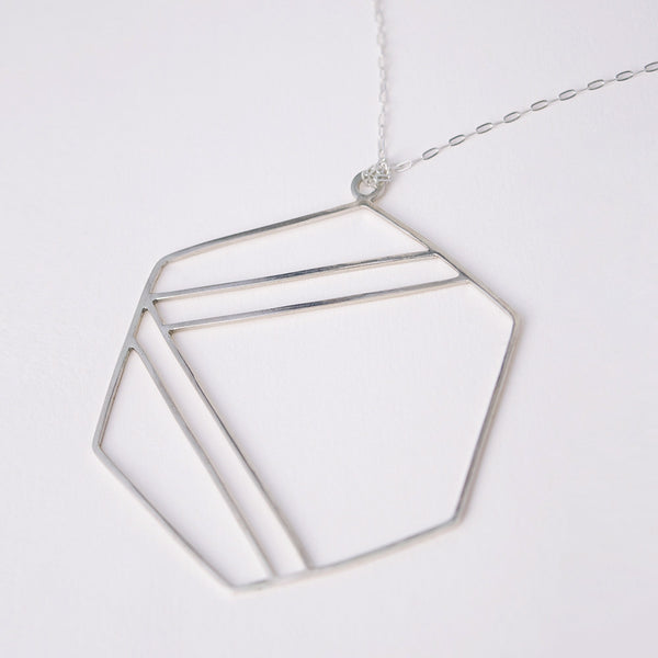 Sterling silver necklace with hexagonal shape outline and center stripe design