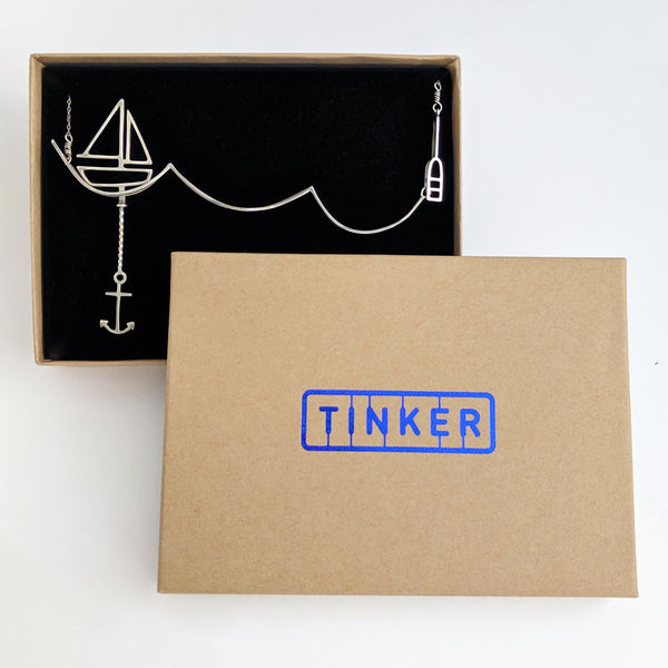 Silver Sailing Necklace with Moving Sailboat from a collection of fun and playful kinetic jewelry by Tinker Company, shown in Tinker gift box. Sustainable jewelry and recycled packaging both made in the Unites States.