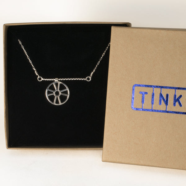 Moving Life Preserver on a Rope Necklace in a Tinker gift box, the pendant is an outline of a ring buoy that moves across a twisted wire rope. From a collection of kinetic jewelry and playful nautical necklaces.