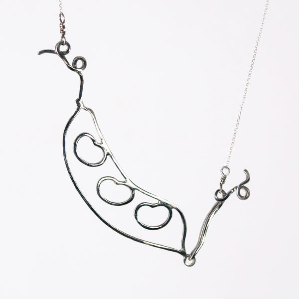 The silver Bean Pod Necklace has an outline of a peapod with three beans on the inside. Symbolic sentimental jewelry that helps you celebrate all the people in your pod. From a collection of fun and playful kinetic silver bean jewelry by Tinker Company.
