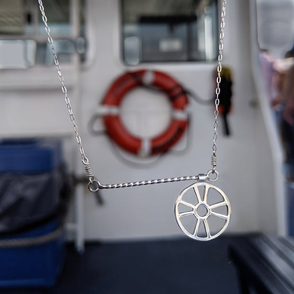 Moving Life Preserver on Rope Necklace has a lifesaver charm that moves across a twisted wire bar necklace designed to look like rope. Shown here on a boat hanging in front of a ring buoy, the inspiration for this piece of fun kinetic jewelry.