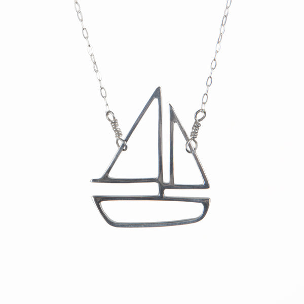 Silver sailboat charm pendant necklace from a collection of storytelling memory jewelry made in New York City by Tinker Company.