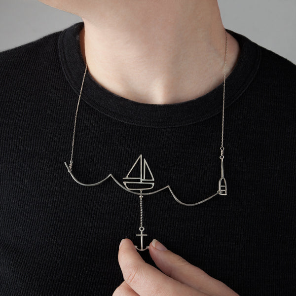 Model wears the Sailing Necklace with a Moving Sailboat and uses the anchor to move the boat across the wave. From a collection of fun and playful kinetic jewelry by Tinker Company.