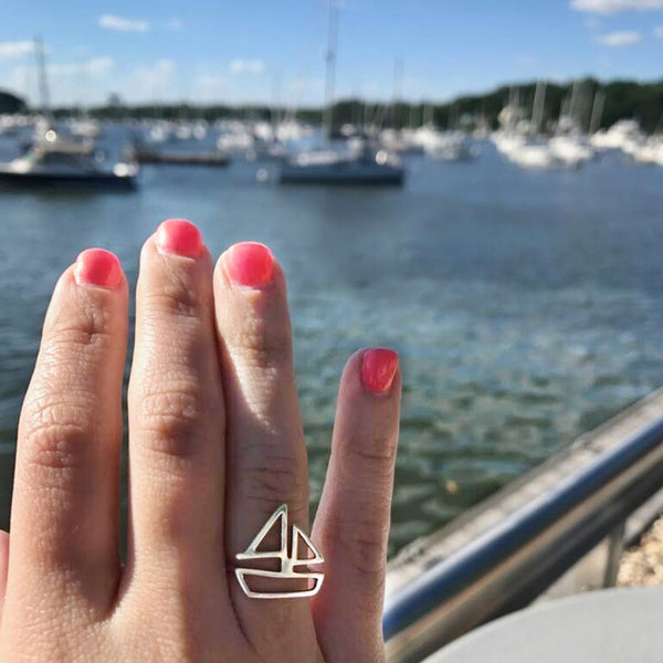 Sailboat Ring in sterling silver by Tinker Company, shown on model's hand at the marina with sailboats and water in the background.