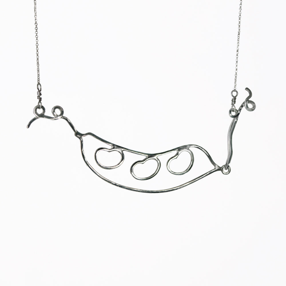 Silver Bean Pod Necklace has an outline of a peapod with three beans on the inside and curling tendrils on the ends. From a collection of fun and playful kinetic silver bean jewelry by Tinker Company.