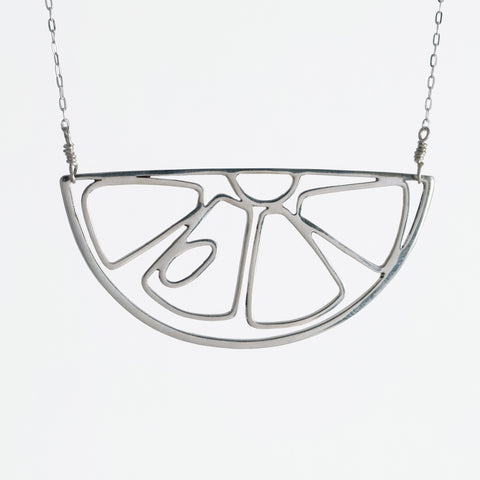 This silver lemon slice pendant, Citrus Slice Necklace, is part of a collection of playful and whimsical fruit jewelry by Tinker Company.