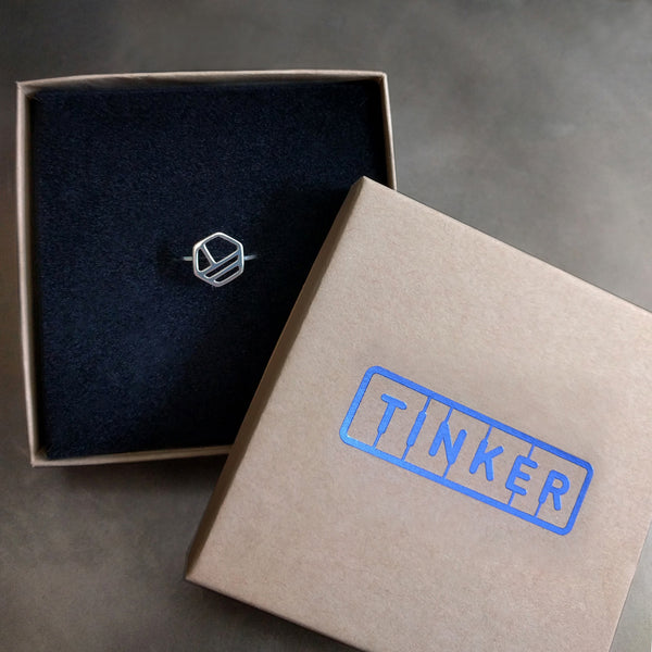 Silver Hexagon Ring with Three Lines, from a collection of minimalist geometric jewelry by Tinker Company. Shown in a Tinker gift box.