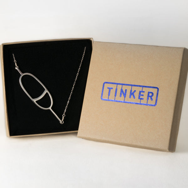 Oval Nautical Buoy Pendant with Stripe in solid sterling silver, shown in a Tinker Company gift box. From a collection of fun and playful nautical jewelry inspired by your favorite memories of summer spent on the water.