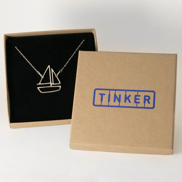 Sterling Silver Sailboat Pendant necklace has an outline of a boat on delicate chain. From a collection of playful sailing memory jewelry shown in a Tinker Company gift box.
