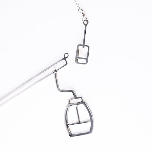 Details of Tinker Company's silver skiing necklace show the moving gondola and ski lift ticket clasp. Fun and playful apres-ski jewelry for snowboarders and skiers with winter vacation wanderlust. Designs that remind you of your favorite memories spent on the mountain.