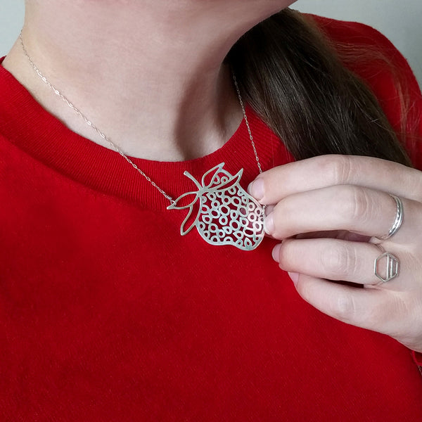 Strawberry Necklace, a fun and playful design from the Crave Collection, shown on model wearing red sweater.