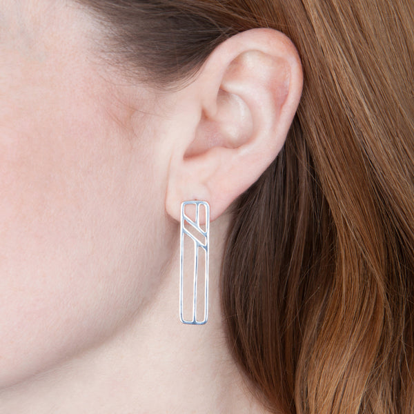 Model wears the Telephone Pole Earrings in sterling silver by Tinker Company. Part of a collection of abstract geometric jewelry celebrating the everyday things that connect us. Minimalist, not meaningless.