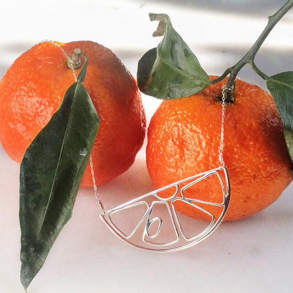 Tinker Company's Citrus Slice Necklace shown with two satsumas