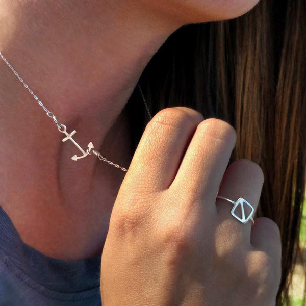 Model wears Anchor Pendant and Overboard Flag Ring, part of a collection of fun and playful nautical jewelry by Tinker Company, celebrating your favorite summer memories on the water.
