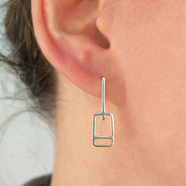 Tinker Company Lift Ticket Earrings as shown on a model's ear. Minimal geometric design made in sterling silver.