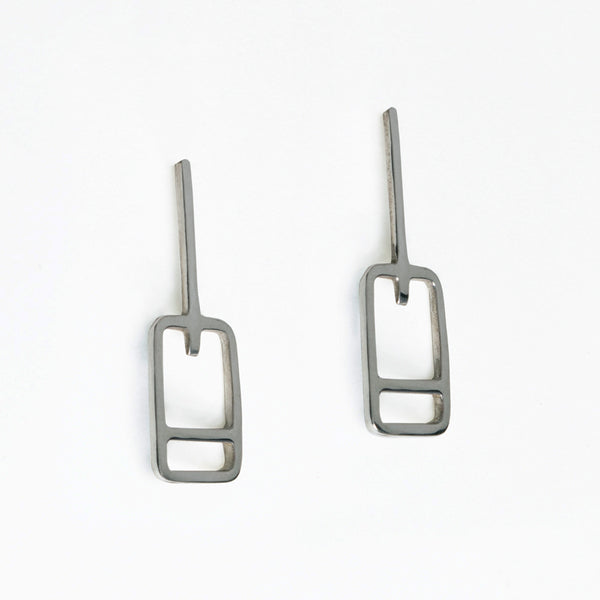 Lift ticket earrings have rectangle shapes with a stripe at the bottom of a line. Designed by Tinker Company, made in recycled sterling silver.