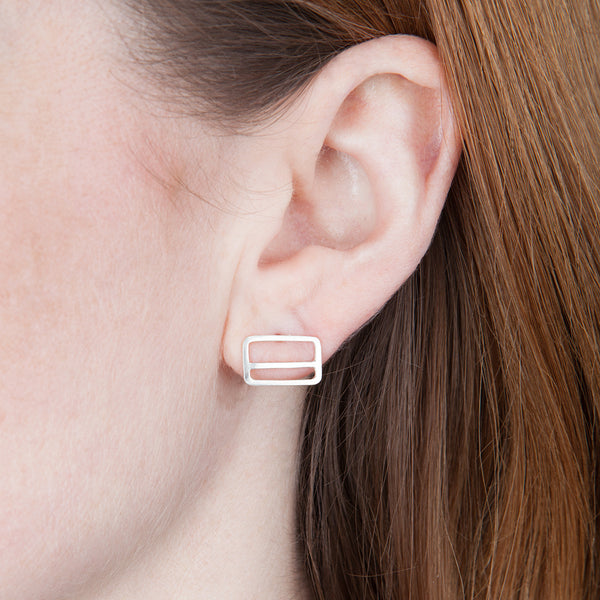 Metrocard Earrings in sterling silver, as shown on model's ear.